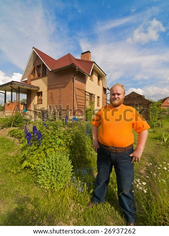 Self-satisfied man standing near his own house.