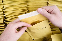 Self sealed mailing envelope quality inspection. Male hands open one yellow bubble mailer out of a bunch of shipping airmail packets. Close-up shot, top view.