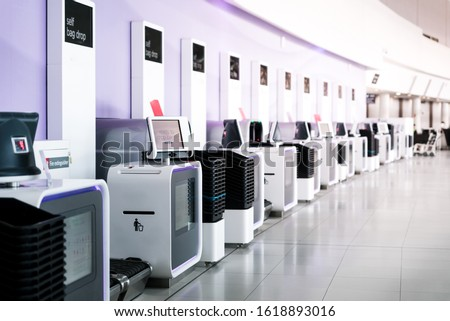 Self service electronic counters for baggage drop at international airport. Self check-in machine. Printing bag tags for passengers