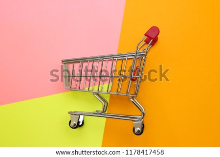 Self-service supermarket full shopping trolley cart on colorful background