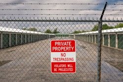 Self storage facility with no trespassing sign on barbed wired fence