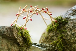 self-supporting bridge by leonardo da vinci built from matches over mossy rocks, selected focus, narrow depth of field