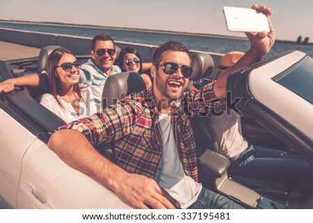 Selfie again! Group of young happy people enjoying road trip in convertible and making selfie #337195481