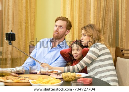 Selfie, family making funny faces. Parents and daughter, dinner table. Child in all of us.