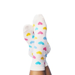 Selfie feet wearing white socks with pastel heart shape pattern isolated on white background. Hipster lifestyles.