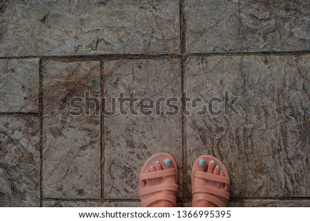 Selfie female legs in sandals with a beautiful blue pedicure on the background of paving slabs.