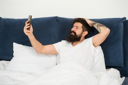Selfie first thing in the morning. Bearded man take selfie in bed. Happy hipster smile to camera phone. Video selfie. Selfie for blog. Social network. Weblog. Modern life. New technology.