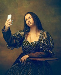 Selfie for gram. Young woman as Mona Lisa, La Gioconda isolated on dark green background. Retro style, comparison of eras concept. Beautiful female model like classic historical character, old