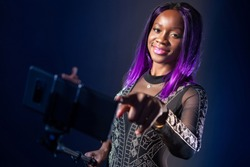 Selfie girl. African woman smiling at the camera phone on a selfie stick. Exotic black girl with purple hair. Selfshot.