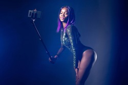 Selfie girl. Black afro model takes a photo with a selfie stick. Girl in a black bodysuit posing. Selfshot. Portrait with a selfie stick. Photo for social networks. Egomania. Fashion trend.