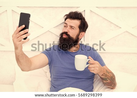 Selfie kiss. Bearded man take selfie in bed. Hipster smile to selfie camera in mobile phone. Enjoying selfie session. Morning coffee routine. Modern life. New technology. Social network.