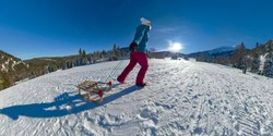 SELFIE, LENS FLARE, OVERCAPTURE: Young woman on relaxing vacation in the Slovenian mountains drags her wooden sled up a snowy hill on a sunny winter day. Tourist walks uphill during a sleighing trip.