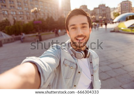 Selfie mania! Excited young guy is making selfie on a camera. He is wearing casual trendy wear and big modern headphones, on a walk in spring town outdoors