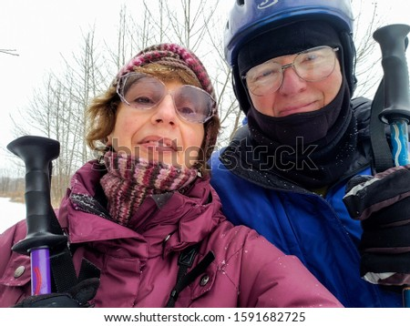Selfie of a senior man and senior woman skiers on cold snowy day; both hold ski poles