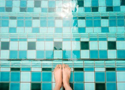 Selfie of feet and legs in green swimming pool and waves background or texture. Top view. Beautiful young female barefoot under aqua water on summer holiday. Woman is wetting toes for relaxing concept
