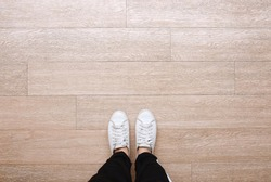Selfie of feet in fashion sneakers on wooden floor background, top view with copy space, social distancing keep distance in public