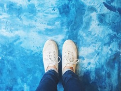 Selfie of feet in sneaker shoes on blue concrete floor background, top view and copy space, social distancing keep distance in public