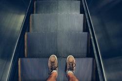 Selfie of feet in sneaker shoes on escalator steps, top view in vintage style