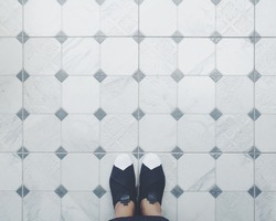 Selfie of feet with black and white sneaker shoes on art pattern tiles floor, top view. slip on shoes.