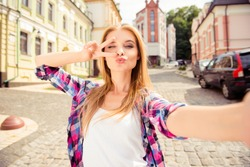 Selfie of funny attractive girl pouting and showing v-sign