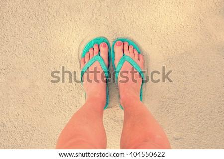 d931a601da0fc Selfie of woman feet wearing flip flops on a beach