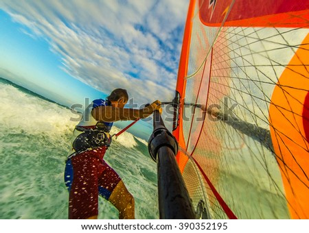 Selfie photo of windsurfing riding on colored sail