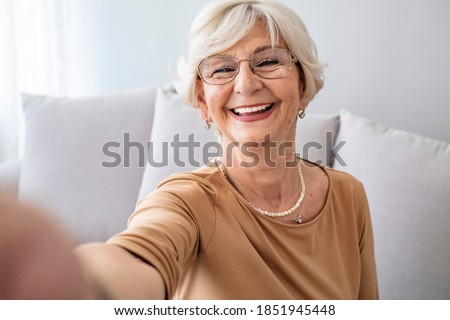 Selfie Portrait of Happy Senior Woman With Gray Hair at home. Portrait of elderly woman with short white hair wearing white glasses and light blouse holding camera and taking selfie.