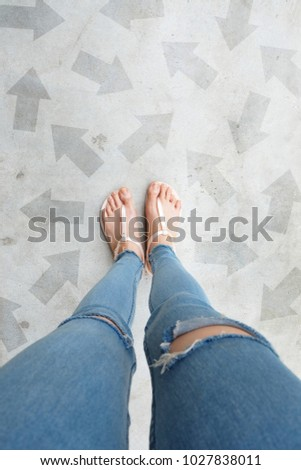 Selfie Shoes with Direction Arrows Choices. Woman Feet and Sandal Standing on Concrete Road Background Great for Any Use. #1027838011