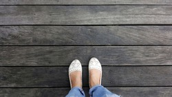 selfie shot of feet woman wearing white shoes and blue jeans standing on wooden floor