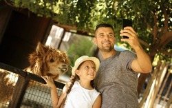 Selfie time! Family and holiday concept. Cute father with daughter feeding  their  friend lama, smiling and have fun in the zoo. Cool weekend