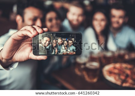 Shutterstock Selfie time! Handsome friends making selfie and smiling while resting at pub.