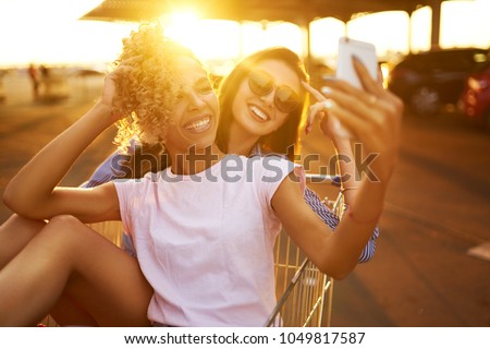 Selfie time! Two beautiful girls having fun on shopping trolleys. Multiethnic young people racing on shopping cart. Beautiful summer day with sunlight. Lifestyle concept.