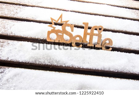 Selfie with snow at Christmas. Wooden letters on a snow-covered board. Conceptual photo Christmas still life.