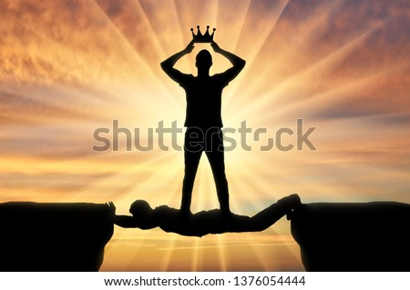 Selfish man puts a crown on his head, he stands on a man in the form of a bridge over a precipice. Concept of selfishness Stock photo ©