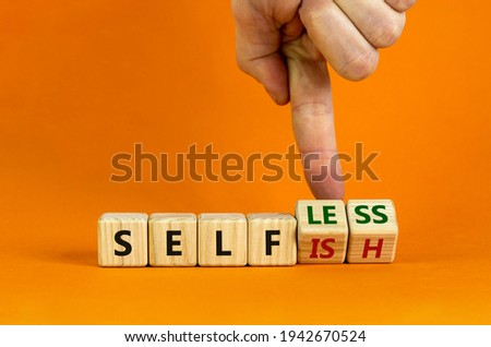 Selfish or selfless symbol. Businessman turns cubes and changes the word 'selfish' to 'selfless'. Beautiful orange background, copy space. Business, psuchological and selfish or selfless concept. Stock photo ©