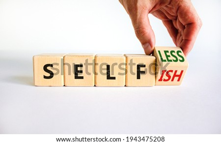Selfish or selfless symbol. Businessman turns cubes and changes the word 'selfish' to 'selfless'. Beautiful white background, copy space. Business, psuchological and selfish or selfless concept. Stock photo ©
