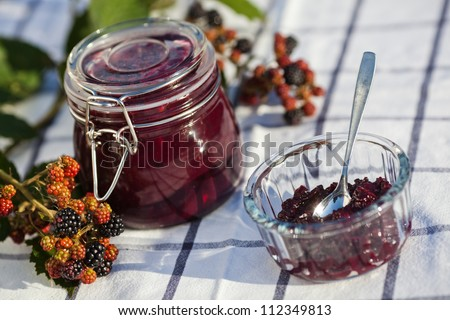 selfmade blackberry jam in a jam jar and in a bowl decorated with blackberry fruits