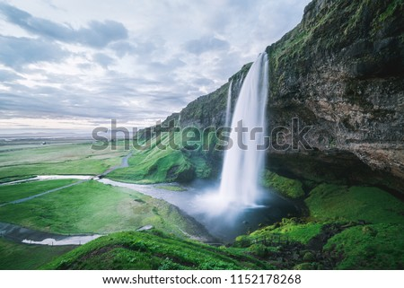 Seljalandsfoss waterfall. Summer landscape with cascade and a river. Famous tourist attraction of Iceland