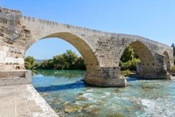 Seljuk Bridge in Aspendos. The Eurymedon Bridge. Turkey. Crooked bridge. An ancient building across the Kopruchay river. The bridge is built of large stone blocks and has five arches