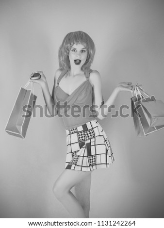 Sell-out. Woman with shopping bags. Girl wearing red wig and fashionable clothes. Fashion shopper with surprised face on pink background. Sale and black friday. Holidays celebration concept. #1131242264