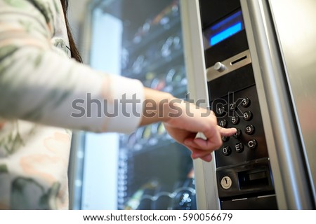 sell, technology and consumption concept - hand pushing button on vending machine operation panel keyboard