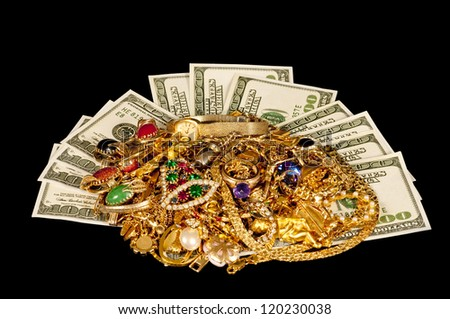 Sell your old gold jewelry for cash.  Here is some hundred dollar bills laying under a heap of gold jewelry.  Shot on a black cloth background. Focus is on the front of the jewelry.