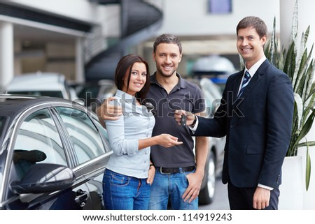 Seller and a couple of with the keys to car