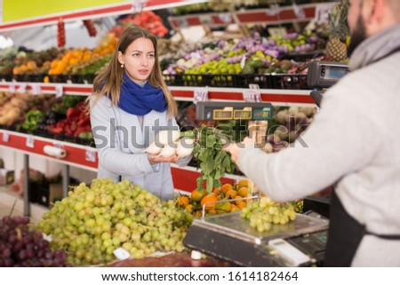 Seller assisting customer to weigh radish
