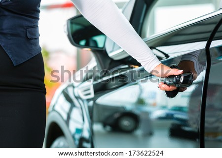 Seller or car salesman and customer in dealership they shaking hands hands over the car keys and seal the purchase of the auto or new car