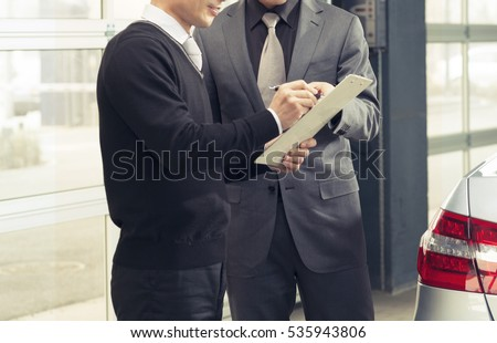 Seller or car salesman explaining the term and condition to the customer in car showroom #535943806