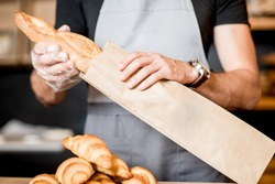 Seller packing bread into the paper bag in the bakery shop, close-up view on the bag with copy space