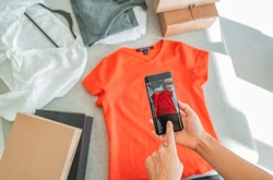 Selling online by taking photo of clothes with phone app and doing e-commerce business woman at home with shipping boxes.