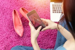 selling online idea concept. online seller use mobile phone take a photo of high heels shoe for upload to online shopping store website.