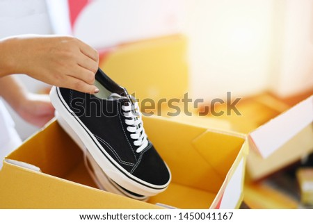 Selling online shopping / Woman packing shoes sneakers in cardboard box prepare parcel box to delivery service customer ecommerce delivery shopping online and order concept